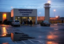 Correctional officers stand at the entrance to the Greensville Correctional Center on Nov. 10, 2009, near Jarratt, Virginia. (Photo by Alex Wong/Getty Images)